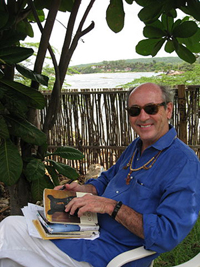 The poet Billy Collins sits in a shady porch overlooking a lake. He's smiling and holding a stakc of his books. He's dressed casually, wearing sunglasses and beaded folk-art jewelry.