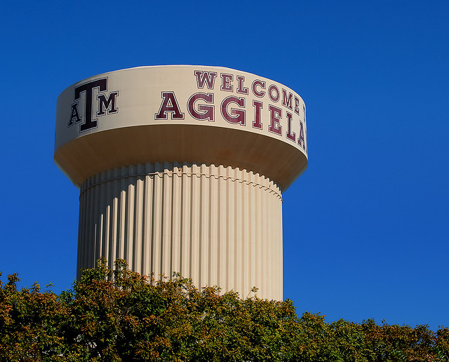 """A photograph of the water tower at Texas A&M in College Station. It reads """"welcome to Aggieland"""" with a Texas A&M logo."""