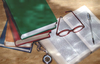A photograph of a table with a stack of books next to book that is open. There is a writing pen, some eyeglasses, and a pocket watch visible as well.