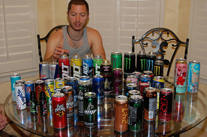 A young man sitting at a table. Every inch of the table is covered with open cans of energy drinks. He reaches for one of the cans.