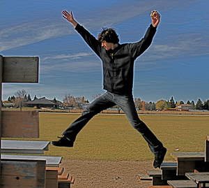 A skinny teenage guy jumps from bench to bench by some outdoor stadium bleachers.