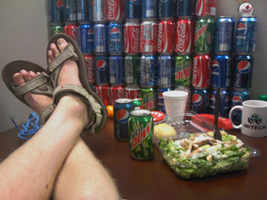 A man eating lunch in his cubical. He's holding the camera himself, so you only see his feet propped up on the table. The wall of the cubical is stacked four high with cans of sodas.