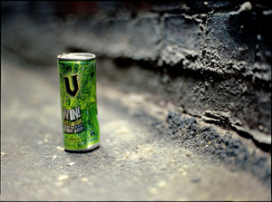 A can of energy drink, crumpled on the side of the road