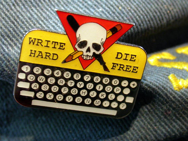 """lapel pin containing a keyboard and, above it, a pencil and pen crossing a skull; the words """"write hard"""" and """"die free"""" on either side of the skull."""