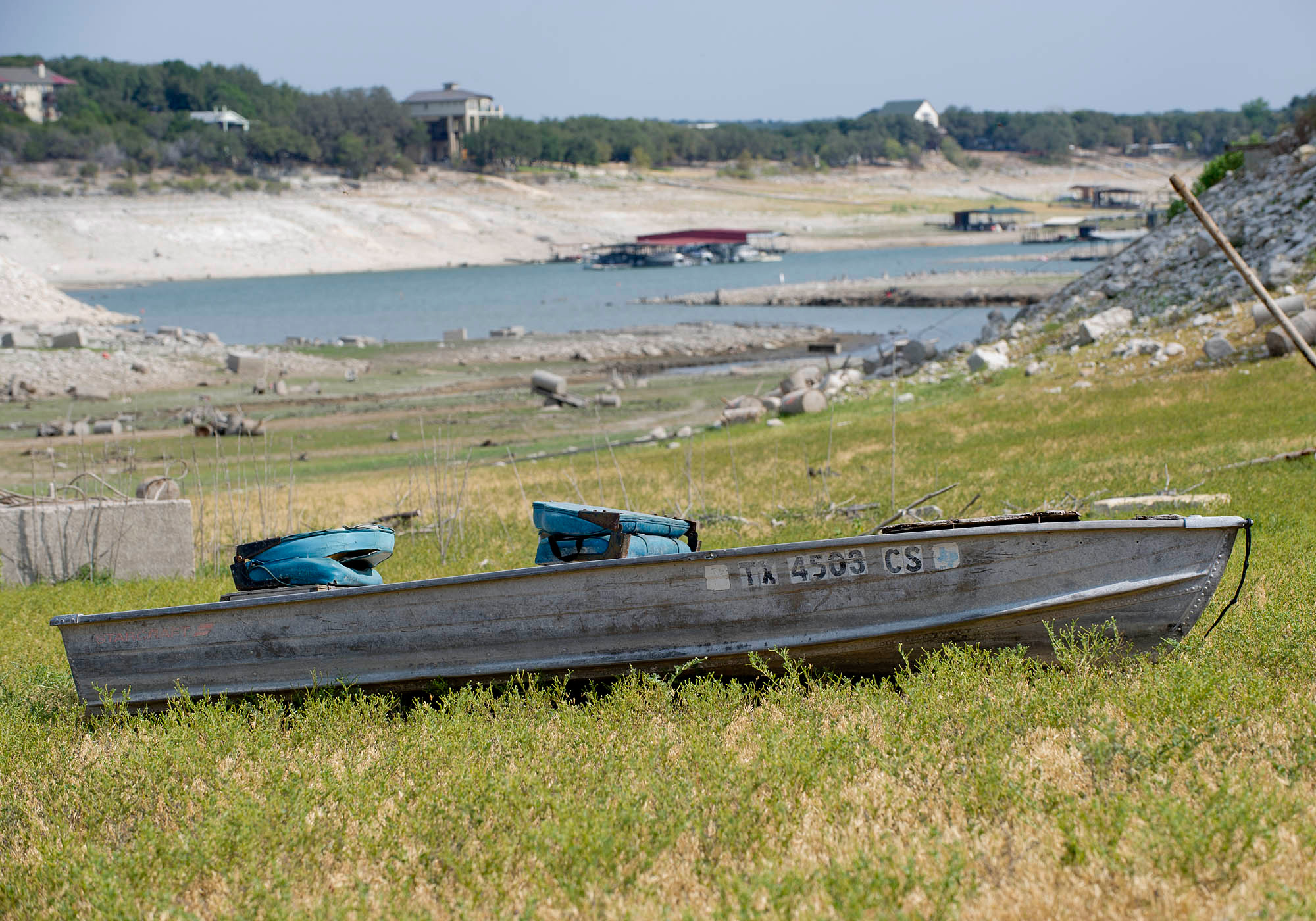 Photo of the dry basin of Lake Travis, near Austin. While there is some water in the bottom of the lake, the picture focuses on a boat that is grounded on a grassy plain.