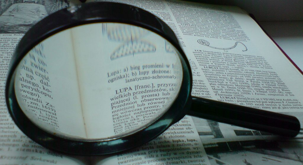 A photograph of a magnifying glass resting on a book, with the print under the magnifier