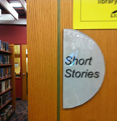 A photograph of the Short Stories section of a library. There is a sign on the side of the bookshelf that reads; Short Stories.