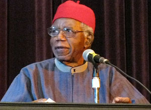 A photograph of the author Chinua Achebe. He is an older man who is wearing traditional African garments.
