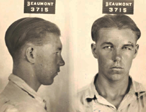An FBI 'mug shot' of Clyde Barrow taken in Beaumont, TX. He is a young man with slicked back hair and a nasty scar above one eyebrow.
