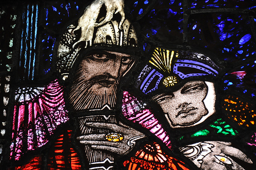 A photograph of a stained glass window panel. In the panel is a serious looking king from an ancient time. Behind him is his queen with a sad look on her face.