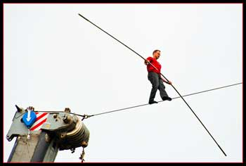 A photograph of a man walking on a tightrope while holding a long balancing pole.
