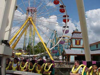 A photograph of Fiesta Texas amusement park. There are numerous rides and a large Ferris Wheel visible.