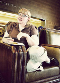 A photograph of a woman sitting on a chair with a notepad and a pen in her hand.