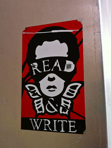 A photograph of a poster that reads: Read & Write. The words are part of an image of a person's head with butterfly wings under it