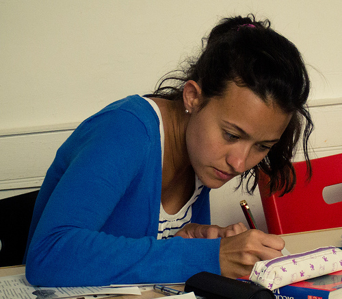 A photograph of a female student writing in a notebook