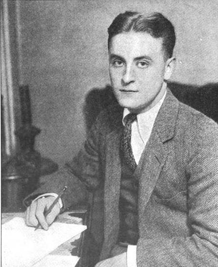 A photograph of F. Scott Fitzgerald taken in the 1920s; he is wearing a suit and tie and is seated at a table with a pen in his hand and paper on the table.