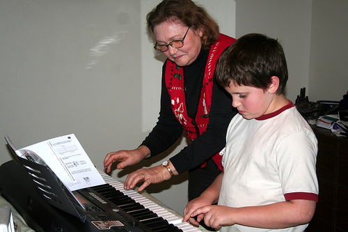 An older woman gives a child piano lessons on a synthesizer keyboard.