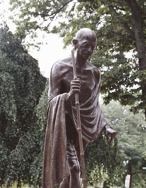 photo of bronze Ghandi sculpture; he walks with a stick, wears glasses, and is wrapped in a robe
