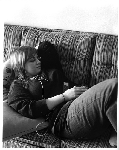 black and white photo of teenage girl reclined on a sofa listen to music through an iPod