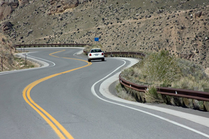 A photograph of a car travelling on a very curvy road.