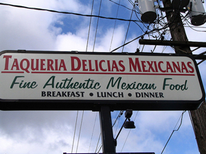 """A photograph of a sign outside of a Mexican food restaurant. It reads: """"Fine Authentic Mexican food"""" or """"Taqueria Delicias Mexicanas""""."""