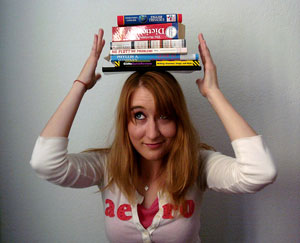 A woman balances a stack of books on her head
