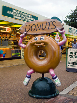 "photo of a donut statue. The donut has arms and legs and holds a ""Donuts"" sign above his head. In the background is a sign over a storefront that reads ""Hot Donuts, Jacket Potatoes, Baguettes"""