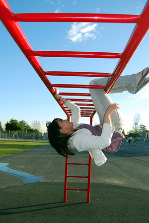 A photograph of a young girl hanging upside down on monkey bars in a playground