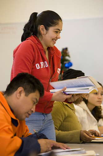 A photograph of a group of students working on assignments in books. One of them is standing and she is holding a book.
