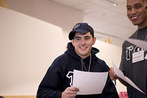 A photograph of two male high school students holding printed pages. They appear to be in a classroom or a hallway.