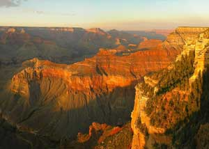 A photograph of the Grand Canyon at sunset. The setting sun has created dramatic shadows throughout the picture.