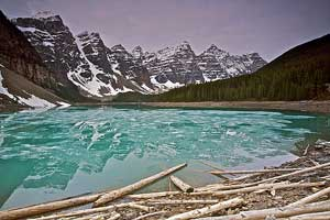 Photo of blue, half iced over lake, brown and white foreboding mountains, and gray sky
