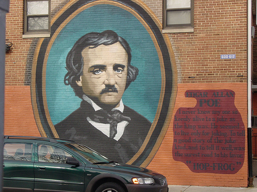 A painting portrait of Edgar Allen Poe on the side of a building