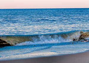 A photograph of a small wave as it approaches the beach