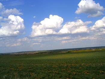 A photograph of a cloudy sky over a prairie