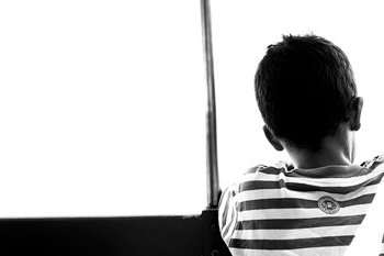 A photograph of a sitting boy taken from behind the subject.