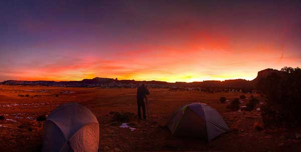 A photograph of a campsite and camper taking a photo of a yellow, orange and pink sunset the glows over the horizon