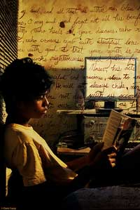 A photograph of a young man reading a book. All around him are hand written notes on every visible surface.