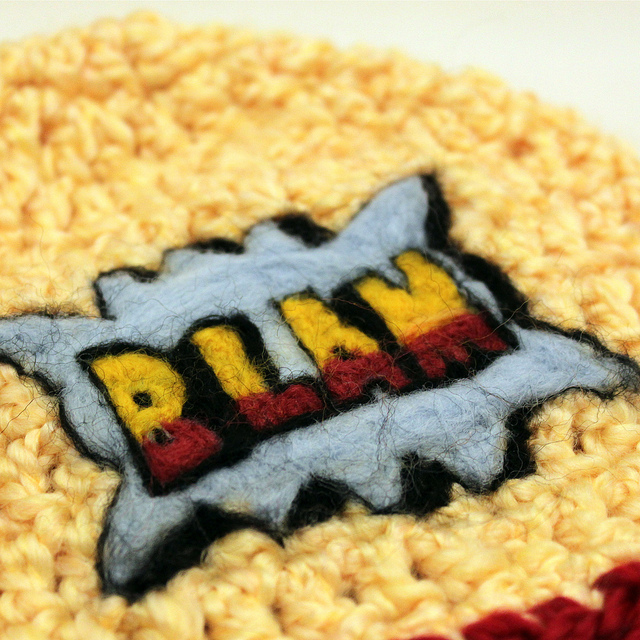 """A patch on coarse fabric bearing the word """"BLAM"""""""