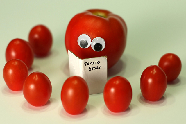 Still-life photo of a tomato with eyes glued on reading a story to smaller tomatoes