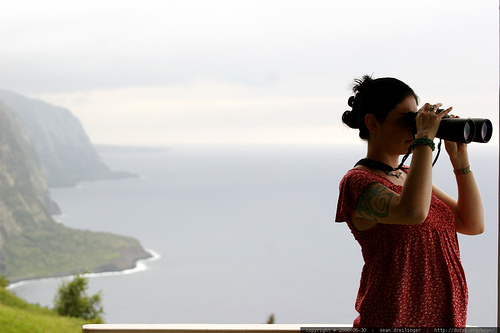 young girl looking through binolculars with a mountainous coast behind her