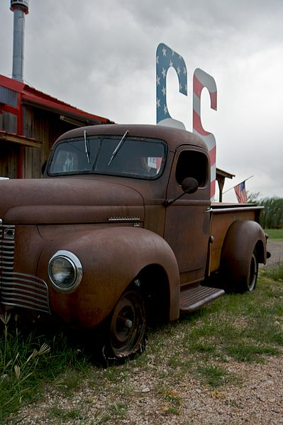 An old, rusted truck in front of a building