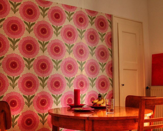 A room with dingy wallpaper that bears a pattern of large, pink flowers
