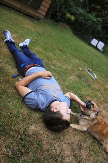 photo of a boy lying on the grass as dark nears. He pets a dog that lies near his head.