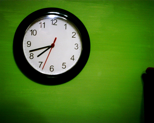 photo of a round clock with a black rim and a white face and black numbers and hands. It hangs on a lime green wall
