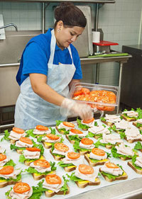 A photograph of a cafeteria worker preparing sandwiches