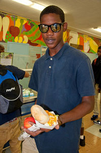 A photograph of a student holding his lunch out in front of him. He is standing in a school cafeteria.