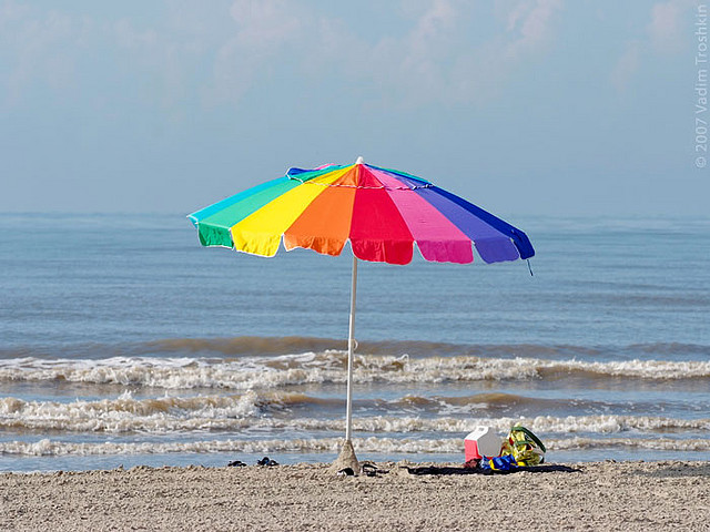 A photograph of a beach umbrella in the sand near the edge of the waterline on a Galveston Island beach.