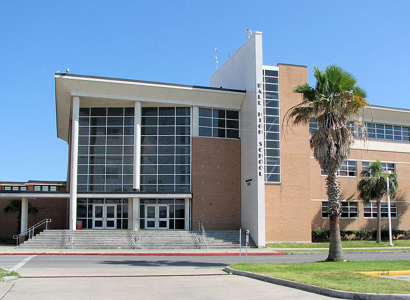 A photograph of a High School from the outside Shown is the main entrance and the stairs leading up to it.
