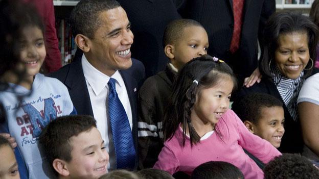 President Barack Obama and family smiling among spectating children